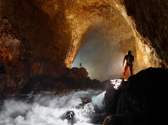 Cavers light the entrance passage of Ora Cave.